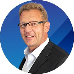 Foto von Peter Sonneck, ein lächelnder blonder Mann mit Brille, schmale Fassung, er ist ca 50 Jahre alt